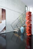 Red sculpture, floating staircase and black floor