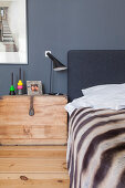 Wooden trunk used as bedside table next to bed against grey wall
