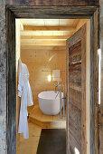 View into wood-clad bathroom through rustic wooden door
