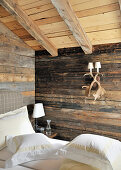 Sconce lamp made from antlers on rustic wooden wall in bedroom