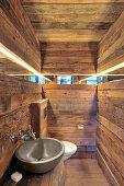 Narrow mirrored strip running along three rustic wooden walls in bathroom