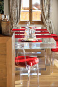 Transparent, modern dining set with red cushions and red place mats