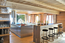 Barstools at counter in front of open-plan stainless-steel kitchen