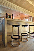 Modern barstool at wooden counter below wood-beamed ceiling