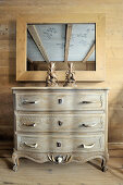Chest of drawers with handles made from branches below mirror on wooden wall