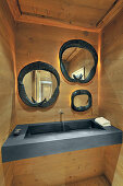 Three mirrors with frames made from antlers above sink