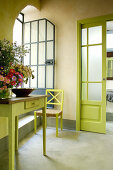 Bright green sliding door, chair and old table with vase of flowers