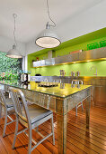 Mirrored table in kitchen with stainless steel cabinets and bright green wall