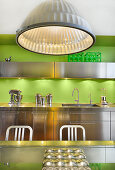 Metal ceiling lamp in stainless steel kitchen with bright green wall