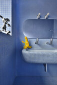 Blue mosaic tiles covering all surfaces in bathroom with rounded edges