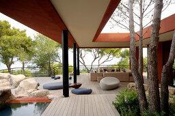 Bäume wachsen durchs offene Dach der überdachten Terrasse