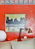 Painting on red-painted wall with reading lamp on shelf at head of double bed