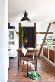 Traditionelle Landhausküche mit Fachwerkwand, Kohlkopf auf Fliesenboden und Holztisch mit Blume