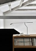 Designer desk lamp on magazine shelves next to black solid balustrade in loft apartment