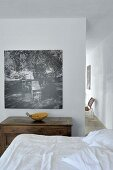 Antique wooden trunk below black and white photo on wall in minimalist bedroom
