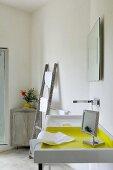 Sink next to vintage ladder and vase of flowers on top of corner cabinet