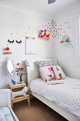 White bed with dotted bed linen, next to it a bedside table with a dog figure in the children's room