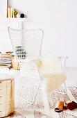 Weißer Outdoor-Stuhl mit Felldecke und Sitzpouf in Goldfarben