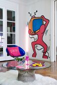 Pop-art mural on wall behind round glass table