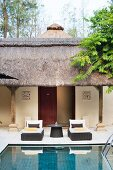Loungers next to pool in courtyard with traditional thatched arcade