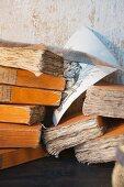 Stack of books with yellowed pages and pen-and-ink drawing against shabby wall