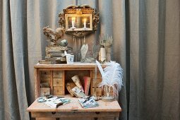 Various vintage accessories on writing desk and gilt-framed mirror sconce in front of grey curtain