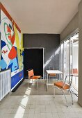 Colourful mural in austere dining room in artist's house