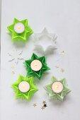 Aus grünem Papier gefaltete Sterne als Teelichthalter
