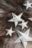Folded white paper stars on fur