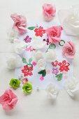 Röschen aus Papier auf einem mit Blumen bedruckten Blatt