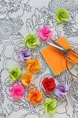 Röschen aus Papier auf einer Folie mit aufgemaltem Blumenmuster
