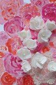 Röschen aus Papier auf gemaltem Blütenmeer