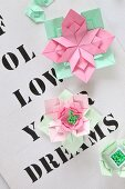 Origami flowers on paper printed with lettering