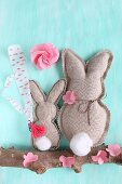 Two fabric rabbits and paper flowers on branch