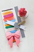 Origami bow and flower on paper with stripes of colour