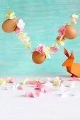 Girlande aus aufgefädelten Papierblüten und Eiern