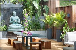 Potted palms, Buddha statue, stools and table on exotic terrace