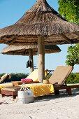 Sun loungers under parasols on sandy beach
