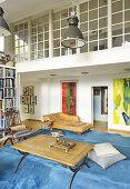 Blick vom Wohnzimmer mit blauem Teppich auf verglaste Galerie