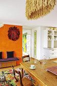 Holztisch mit Stühlen auf buntem Teppich und lila Sitzbank vor orangefarbener Wand