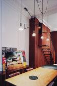 Tisch mit Lederstühlen unter Pendelleuchten, im Hintergrund Treppe