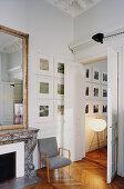 Kamin mit Spiegel, grauer Armlehnstuhl und Bildergalerie neben geöffneten Flügeltüren