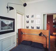 Doppelbett mit Leselampen und Betthaupt aus Holz in offenem Schlafraum