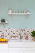 Peppers and jars on wooden worksurface with cement-tiled splashback below cups on bracket shelves on pale blue wall