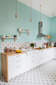 White cupboards, pale blue wall and patterned cement tiles in kitchen