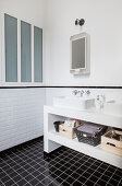 Twin sinks on washstand in black and white bathroom