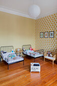 Twin beds in children's bedroom with wallpaper on accent wall in period apartment
