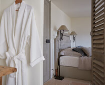 View into bedroom with double bed and standard lamps and dressing gown hung on door in foreground