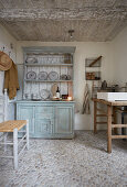 Rustic wooden table with countertop sink and dresser in small room with pebble-cobbled floor