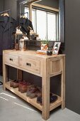 Wooden console table with two drawers and shoe rack below mirror on dark foyer wall